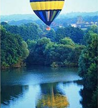 hot air balloon reflected in a lake