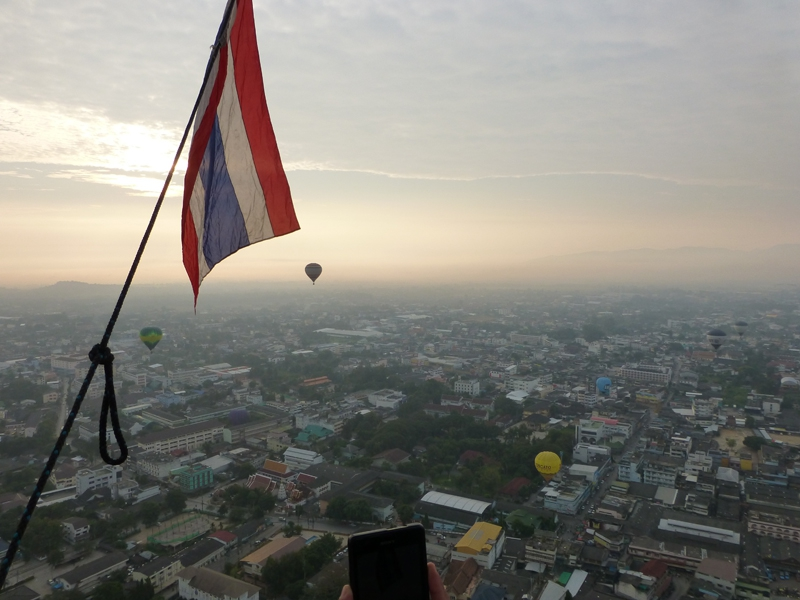 Hot air balloons flying over Chiang Mai in Thailand on an early morning hot air balloon flight. That'll be the Thai flag flying from the balloon basket then!
