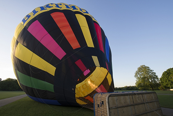 The hot air goes into the balloon and it rises up.