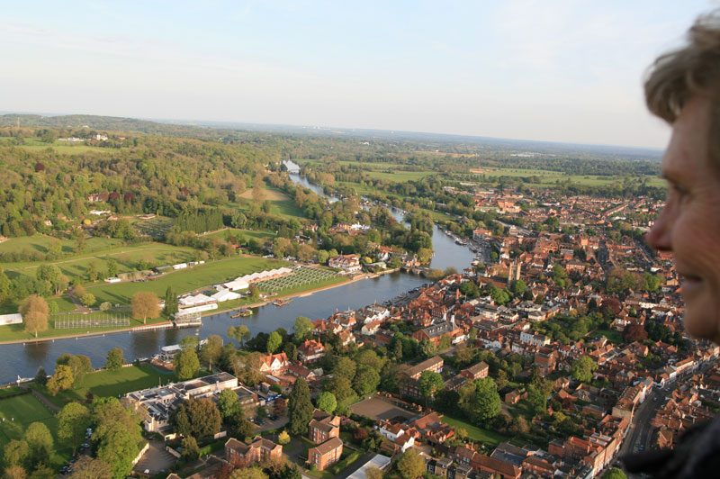 One of our hot air balloon rides passengers takes in the views of the Oxfordshire market town of Henley Upon Thames, with the river cruise boats of Hobbs of Henley just visible on the right bank beyond the river bridge