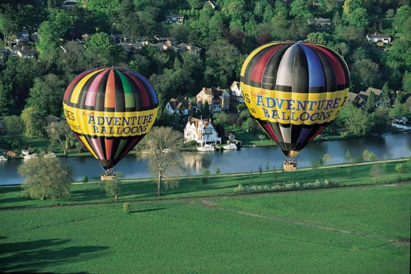 Two of our hot air balloons cross the River thames by the Reading Festival site