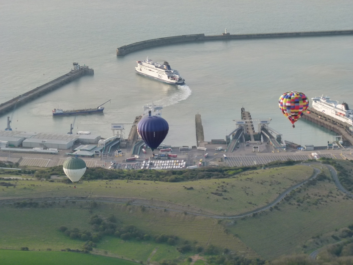Three hot air balloons on a flight over Dover Harbour